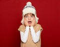 Winter holiday concept - girl in hat and sweater on red background Royalty Free Stock Photo