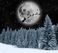 Winter holiday theme background magic with snowflakes pine forest and silhouette of santa claus on the moon Royalty Free Stock Photo
