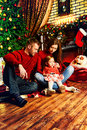 Winter holidays happy family celebrating christmas at home by the fireplace and the christmas tree Royalty Free Stock Photography