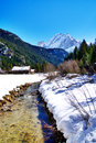 Winter hut huts with a nearby river and surrounding mountains Stock Photos