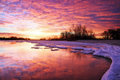 Winter landscape with lake and sunset fiery sky. Royalty Free Stock Photo