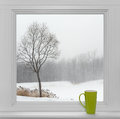 Winter landscape seen through the window and green cup Royalty Free Stock Photo