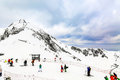 Winter landscape. Snow covered high mountain peaks under cloudy panoramic skies in Europe. Downhill skiers and snowboarders.