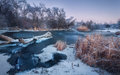 Winter landscape with snowy trees, beautiful frozen river at dusk Royalty Free Stock Photo