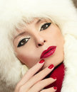 Winter makeup with red lips and fingernails on a beautiful young girl Royalty Free Stock Photos