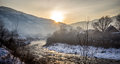 Winter mist landscape with mountains river and houses Royalty Free Stock Images