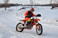 Winter motocross racer on a motorcycle rides in turn of with the demolition the rear wheel the snow covered road the reversal Royalty Free Stock Images