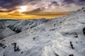 Winter mountains with frozen snow and icing at sunset