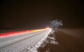 Winter night driving car light in on ice road in snow Stock Photos