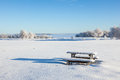 Winter park bench in deep snow in the field Stock Photo