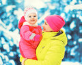 Winter portrait happy smiling mother holds baby on her hands over snowy christmas tree Royalty Free Stock Photo