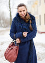 Winter portrait of woman at wintry city in blue coat street Royalty Free Stock Image
