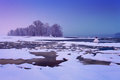 Winter river with cracked ice and light after sunset in haze Royalty Free Stock Images