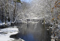Winter river scene snow and ice covered trees hanging over an open making a Stock Image