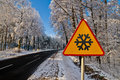 Winter road, driving through snowy forest, warning sign Royalty Free Stock Photo