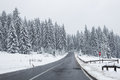 Winter road a in mountain through middle of the forest Royalty Free Stock Image