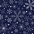 Winter seamless pattern with different snowflakes on dark blue background