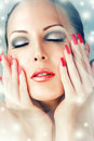 Winter skin care beautiful female face with red lips and long lashes long false nails Royalty Free Stock Images