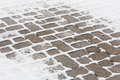 Winter snow covering a brick sidelwalk sidewalk pavers with in the cracks during the Royalty Free Stock Image