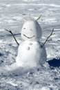 Winter snowman with a beaming smile and sticks for arms and hair in a flat snowy field in sunshine Royalty Free Stock Images
