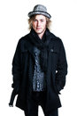 Winter in style image of a caucasian man with grungy blond hair dressed warmly a stylish black trench coat and a funky hat and Royalty Free Stock Photography