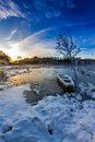 Winter sunrise over the frozen lake with boat Royalty Free Stock Images