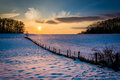 Winter sunset over a fence and snow covered farm field in rural Royalty Free Stock Photo