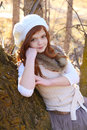 Winter teen girl leaning against a large tree Stock Images