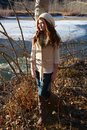 Winter teen girl leaning against a tree with river in the background Royalty Free Stock Photography