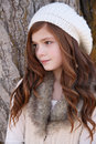 Winter teen girl standing against a large tree Royalty Free Stock Photography