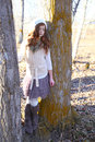 Winter teen girl standing between two large tree trunks Stock Images