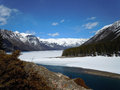 Winter thaw frozen river beginning its spring in the canadian rockies Stock Images