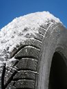 Winter tire closeup of car tyre covered with snow shot on blue background Royalty Free Stock Photos