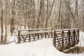 Winter trail a snowy scene along a wooded park includes fresh snow with a bridge crossing a small side stream Royalty Free Stock Photo