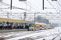 Winter train delay a arrives late at a snowy station with people waiting in leiden in Royalty Free Stock Photo