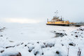 Winter travel ship through frozen sea with snow ice and rocks Royalty Free Stock Images