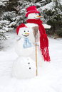 Winter - two snowmen in a snowy landscape with a hat and a red s Royalty Free Stock Photo