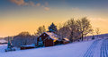 Winter view of a barn on a snow covered farm field at sunset, in Royalty Free Stock Photo