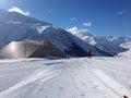 Winter walking in andermatt switzerland a walker makes his way down a snowy multi use trail at the ski resort many swiss ski Stock Photo