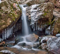 Winter waterfall and icicles surround a of melting snow during a spring thaw of the cascading waterfalls in the patapsco state Royalty Free Stock Photo
