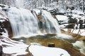 Winter waterfall.  Small pond and snowy boulders bellow cascade of waterfall. Crystal freeze water of mountain river and sounds. Royalty Free Stock Photo