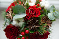 Winter wedding bouquet of red roses with wedding rings. Royalty Free Stock Photo