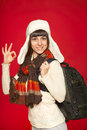 Winter woman tourist with backpack young smiling gesturing ok over red background Royalty Free Stock Images
