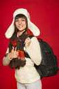 Winter woman tourist with backpack young smiling over red background Stock Images