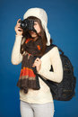 Winter woman traveler with photocamera girl looking through the viewfinder over blue background Stock Image
