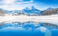 Winter wonderland in the Alps reflecting in crystal clear mountain lake Royalty Free Stock Photo