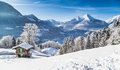 Winter wonderland with mountain chalet in the alps panoramic view of beautiful scenery traditional on a cold sunny day Stock Photo