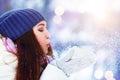 Winter young woman portrait. Winter girl blowing snow. Beauty Joyful Teenage Model Girl having fun in winter park Royalty Free Stock Photo