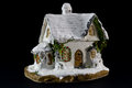 Winters christmas decoration with small toy ceramic house over black background Royalty Free Stock Images