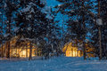 Wintersnowfall night, small wooden houses with warm light Royalty Free Stock Photo